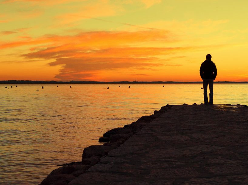 Person standing on a dock looking at the sunset